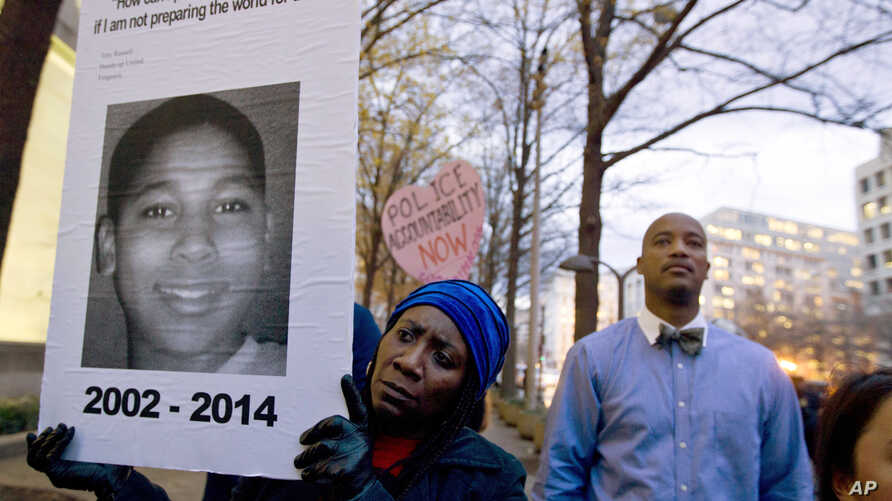 FILE - Tomiko Shine holds up a picture of Tamir Rice, the 12 year old boy fatally shot on Nov. 22 by a rookie police officer, in Cleveland, Ohio, Dec. 1, 2014.