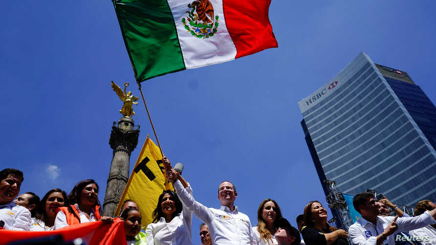 Ricardo Anaya, presidential candidate for the National Action Party (PAN), waves a Mexican flag during his closing campaign rally in Mexico City, Mexico, June 24, 2018.