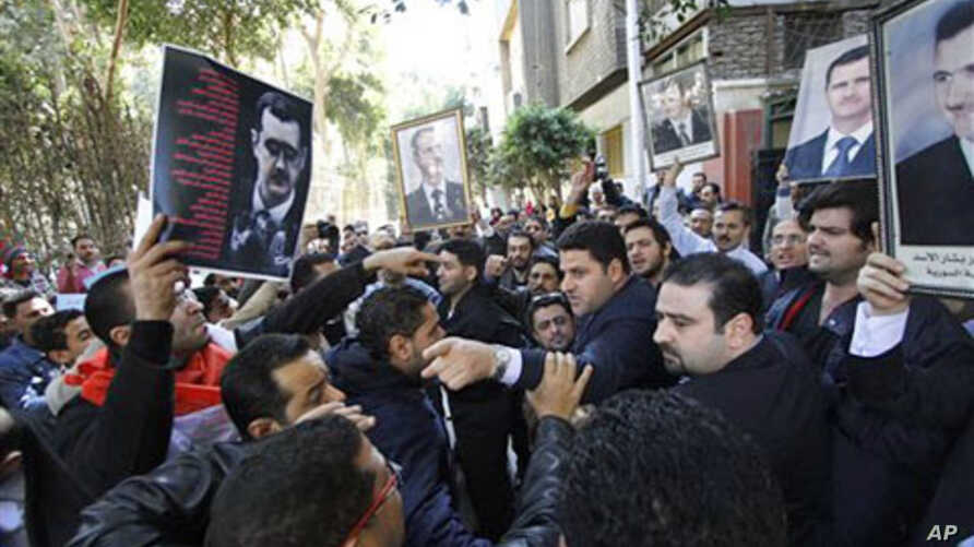 Carrying pictures of Syrian President Bashar Assad, a group of Syrians, some supporters of Assad, right, and some opposed to his regime, left, stage a protest outside the Syrian embassy in Cairo, Egypt, March 15, 2011