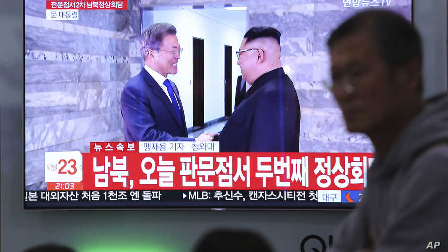 A TV screen shows South Korean President Moon Jae-in, left, meeting with North Korean leader Kim Jong Un at the border village of Panmunjom during a news program at the Seoul Railway Station in Seoul, South Korea,  May 26, 2018. Kim and Moon met for