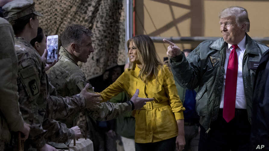 President Donald Trump and first lady Melania Trump greet members of the military as they arrive for a hangar rally at Al Asad Air Base, Iraq, Dec. 26, 2018.