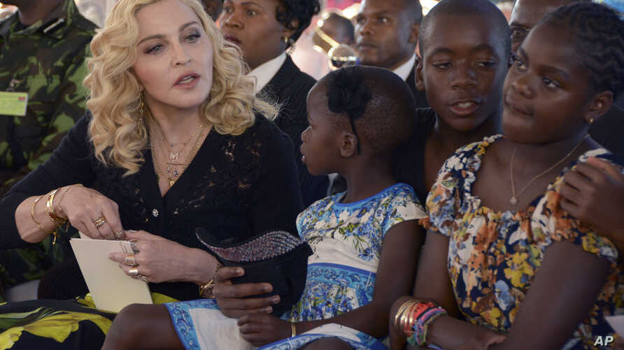 FILE - US musician Madonna, left, sits with her adopted children Stella, David and Mercy, at the opening of The Mercy James Institute for Pediatric Surgery and Intensive Care, located at the Queen Elizabeth Central Hospital in the city of Blantyre, M