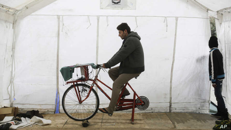 Syrian refugee Odai Ahmed peddles to charge smart phones and batteries inside a tent at the migrants camp near Calais, northern France, Nov. 4, 2015.