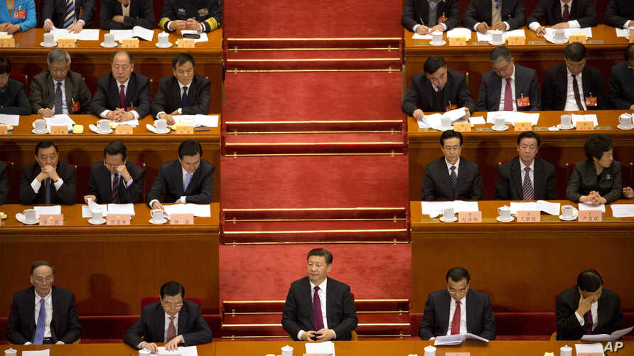 Chinese President Xi Jinping, center, listens to a speech during the opening session of the Chinese People's Political Consultative Conference in Beijing's Great Hall of the People, March 3, 2017.