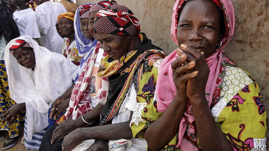 FILE - Women wait outside the workroom of the Multi-functional Platform for Poverty Alleviation in the village of Poa near Ougadougou in Burkina Faso.