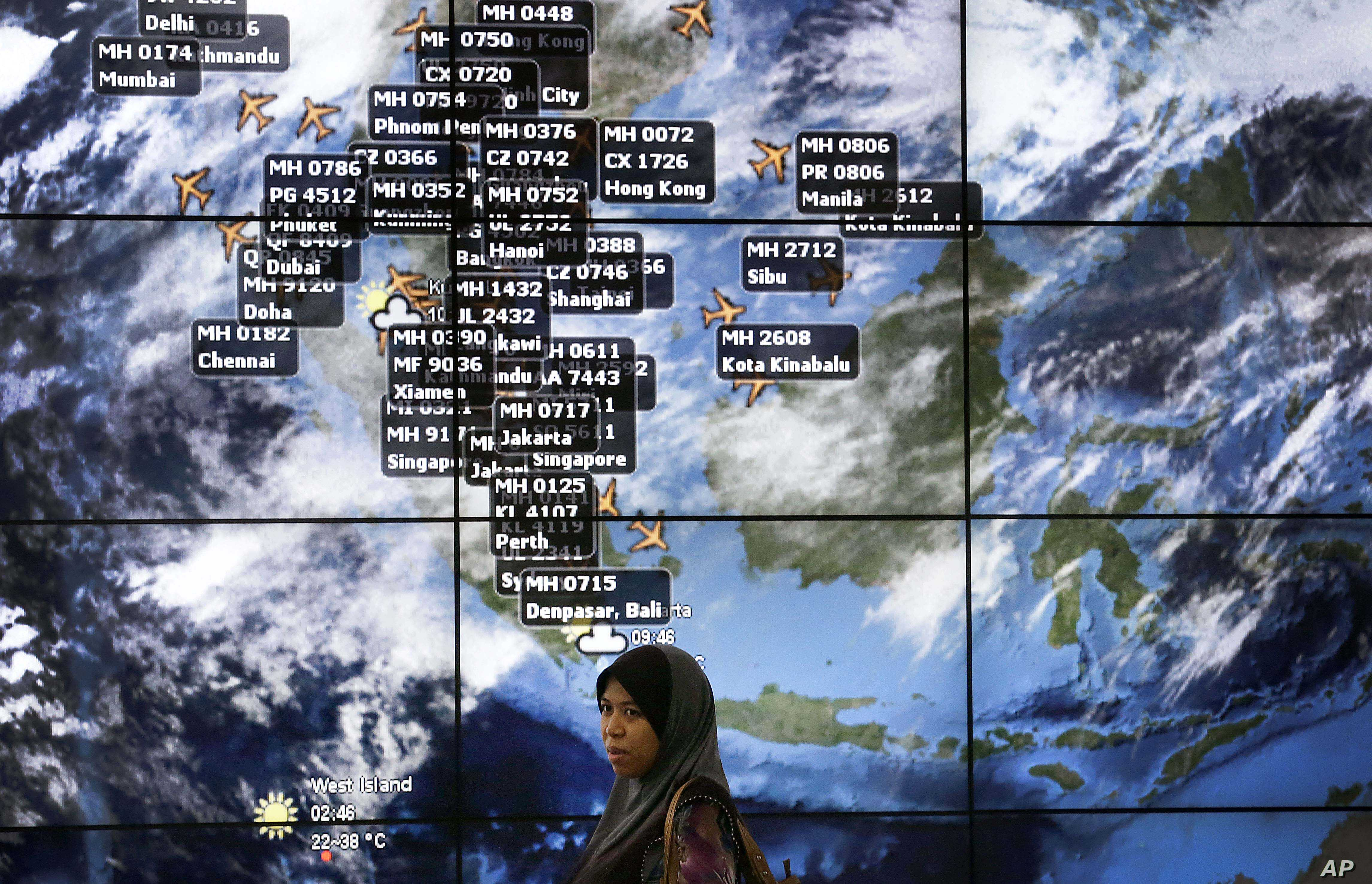 A lady stands in front of an electronic display showing live information of flight positions according to predicted time and flight duration calculations at the Kuala Lumpur International Airport, Sunday, March 16, 2014 in Sepang, Malaysia. Malaysian