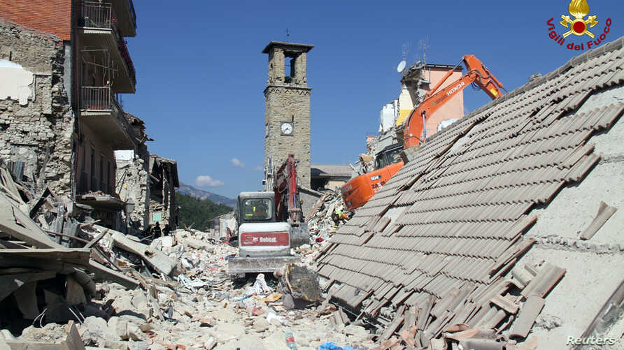 Rescuers work at a collapsed house following an earthquake in Amatrice, central Italy, Aug. 26, 2016.
