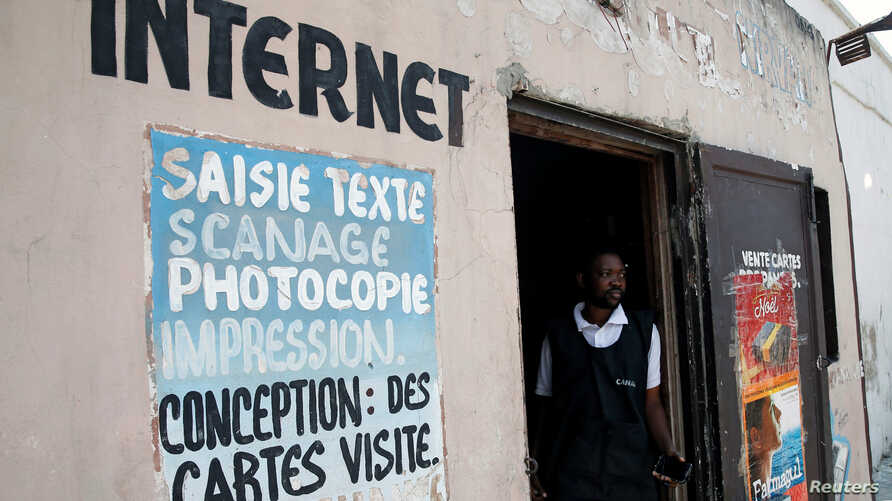 FILE - A Congolese internet cafe owner stands at the entrance of his empty business, in Kinshasa, Democratic Republic of Congo, Jan. 7, 2019.