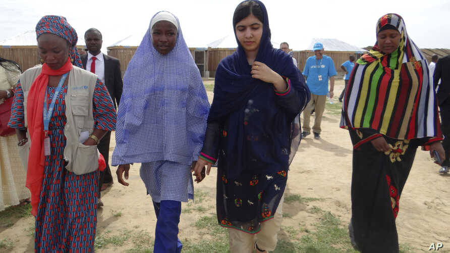 Pakistani activist Malala Yousafzai, center right, is welcomed by students and a staff from UNICEF during a visit to the camp of people displaced by Islamist extremists in Maiduguri, Nigeria, July. 18, 2017.