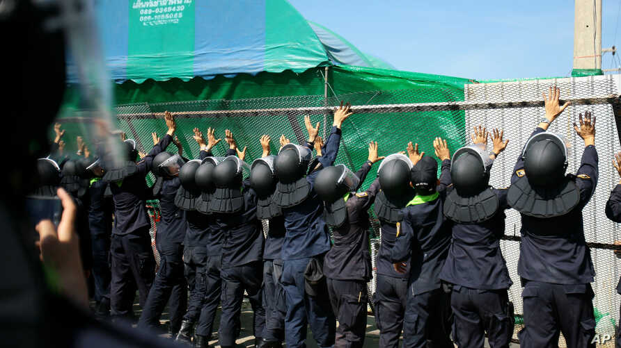 FILE - Police remove a fence to facilitate traffic flow near Wat Phra Dhammakaya temple in Pathum Thani province, north of Bangkok, Thailand, Tuesday, Dec. 27, 2016.