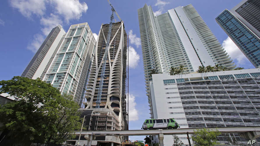 A high-rise building under construction is shown next to high-rise condominium buildings, Sept. 7, 2017, in downtown Miami.