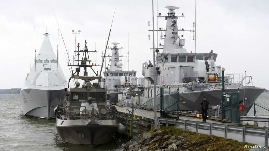 HMS Visby and two minesweepers lie moored at the jetty at Berga marine base outside Stockholm Oct. 22, 2014.