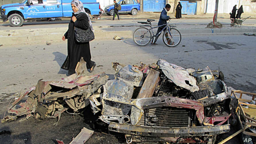 A woman walks past the site of a bomb attack in Baghdad's Shaab District, northern Baghdad, December 22, 2011.
