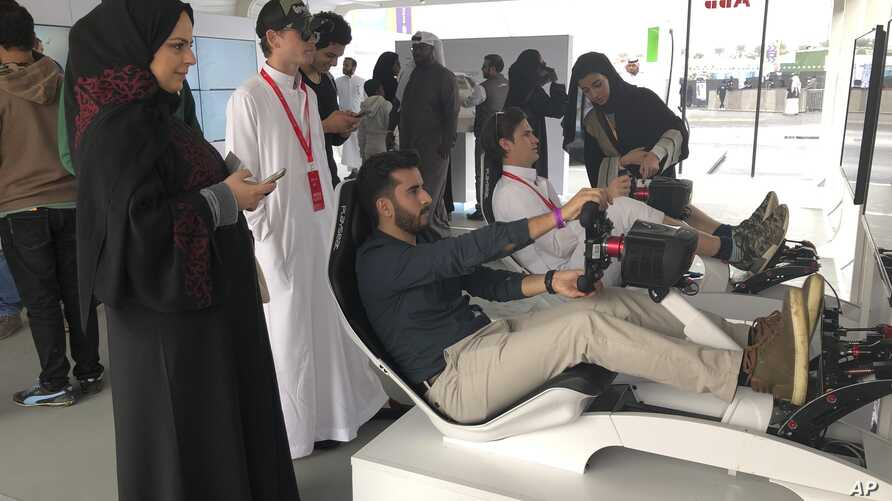 Hostesses in black robes and headscarves give instructions to foreign visitors trying out a simulator at a Formula-E race on the outskirts of Riyadh, Saudi Arabia on Saturday, Dec. 15, 2018.
