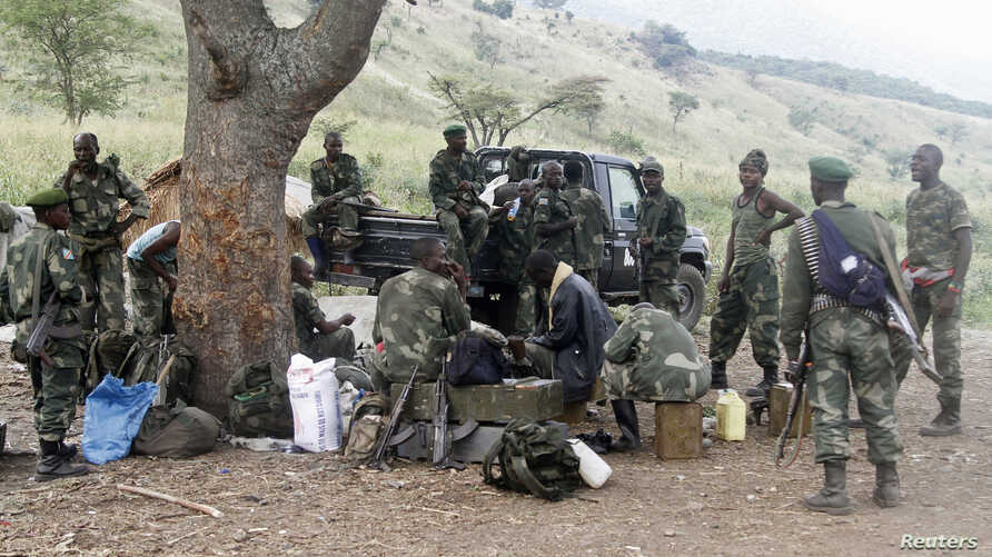 Congolese soldiers from the Armed Forces of the Democratic Republic of Congo take a break during their offence against Democratic Forces for the Liberation of Rwanda rebels in Kirumba village, Rutshuru territory, eastern Democratic Republic of Congo,
