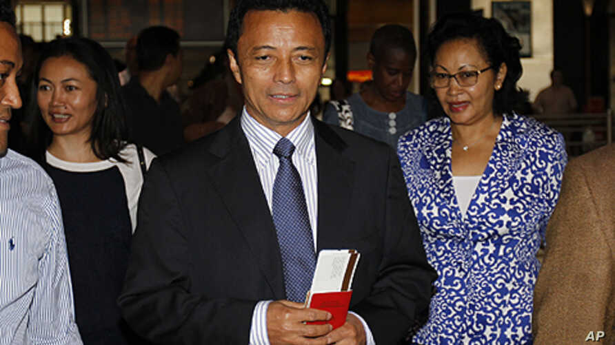 Former Madagascar leader Marc Ravalomanana and his wife Lalao (R) hold plane tickets after checking in at the O.R Tambo airport in Johannesburg, January 21, 2012.