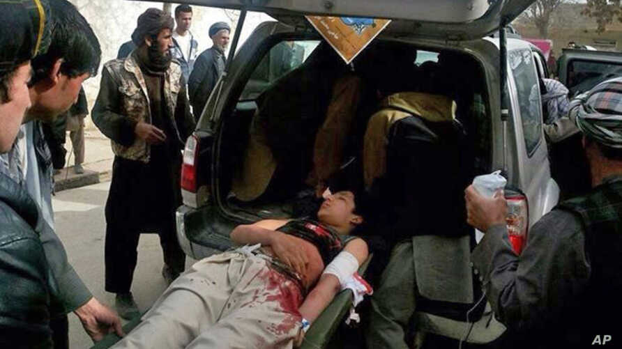 Afghans help an injured man into a vehicle after a suicide attack in Maimana, Faryab province, Afghanistan, March 18, 2014.