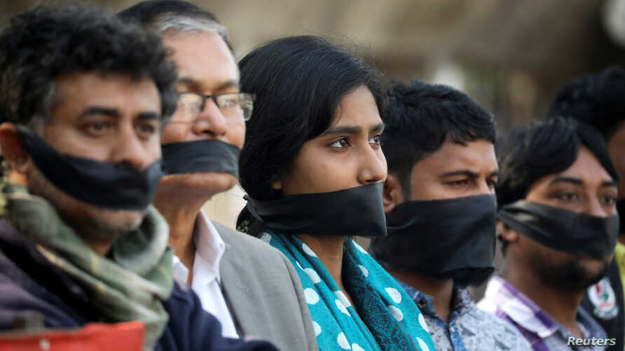 Activists of the leftist alliance cover their mouths with black cloths as they join in a rally to demand a new election under caretaker government, in Dhaka, Bangladesh, Jan. 3, 2019.