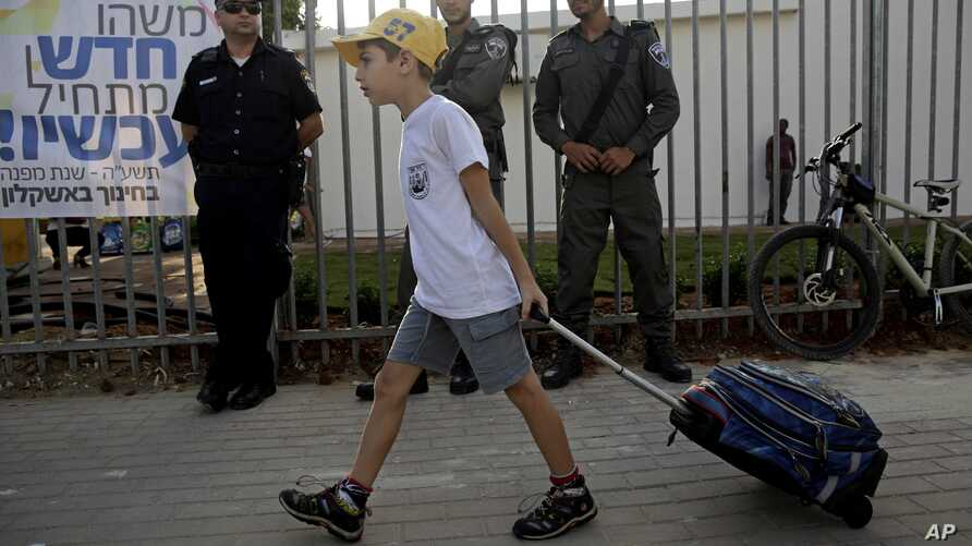 An Israeli student pulls his bag on his way to elementary school as he walks past policemen in the costal city of Ashkelon, Sep. 1, 2014.