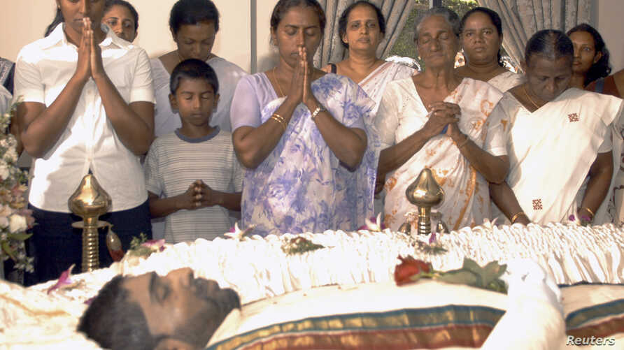 FILE -  The family of Nadarajah Raviraj, a prominent member of the Tamil National Alliance who was assassinated the previous day, pay their respects over his body in Colombo, Nov. 11, 2006.