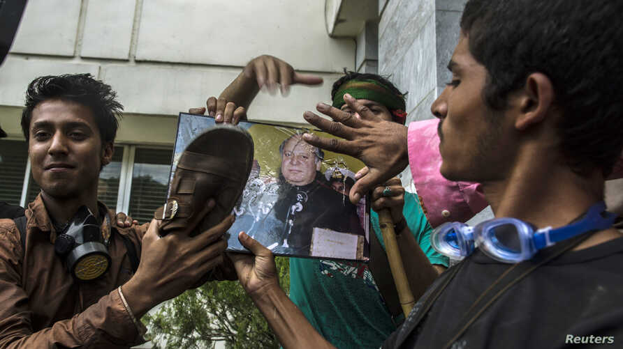 Supporters of Tahir ul-Qadri, a Sufi cleric and leader of Pakistan Awami Tehreek (PAT) party, use a sandal to hit a portrait of Prime Minister Nawaz Sharif, as a sign of disrespect, after storming the building of the state television channel PTV, dur...