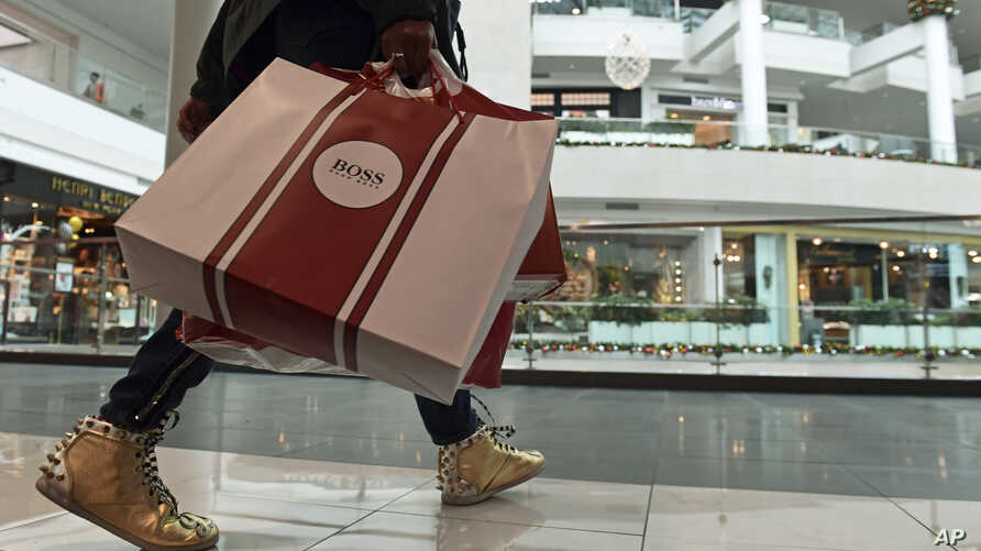 FILE- People shop at the Pentagon City Mall in Arlington, Va., Dec. 22, 2017. On Friday, the U.S. government will publish its snapshot of the first-quarter GDP.