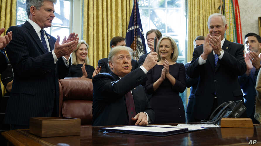 """President Donald Trump holds up a pen during a signing ceremony of the """"Cybersecurity and Infrastructure Security Agency Act,"""" in the Oval Office of the White House, Nov. 16, 2018, in Washington."""