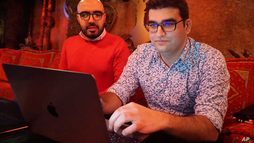 Certfa researchers Nariman Gharib (L) and Amin Sabeti look at a computer at a cafe in London on Dec. 7, 2018.