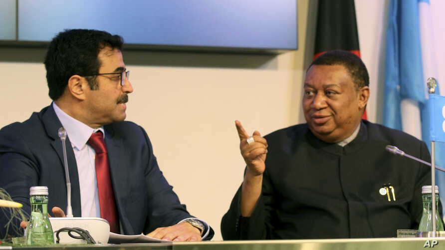FILE - Mohammed Bin Saleh Al-Sada, Minister of Energy and Industry of Qatar and President of the OPEC  talks with Mohammad Sanusi Barkindo, right, OPEC Secretary-General of Nigeria before a news conference after an OPEC meeting at their headquarters