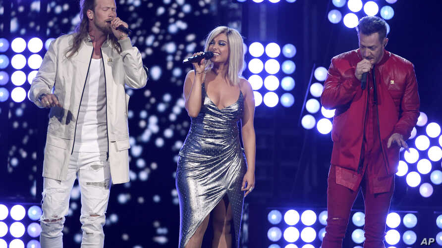 """FILE - Tyler Hubbard, right, and Brian Kelley, left, of Florida Georgia Line, and Bebe Rexha, center, perform """"Meant to Be"""" at the 53rd annual Academy of Country Music Awards at the MGM Grand Garden Arena in Las Vegas."""