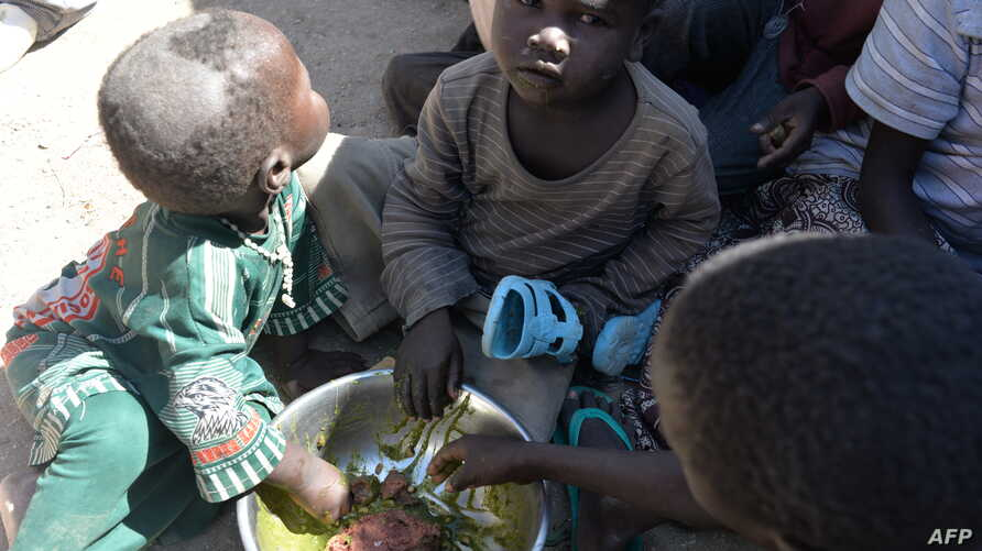 FILE - Children eat on November 13, 2014 in a camp for Nigerian refugees in Minawao, in the extreme north-west of Cameroon.