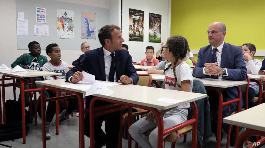 French president Emmanuel Macron looks at Jean-Michel Blanquer, minister of National Education, as they sit in a classroom of a secondary school in Laval, western France, Sept. 3, 2018, at the start of the school year in France.