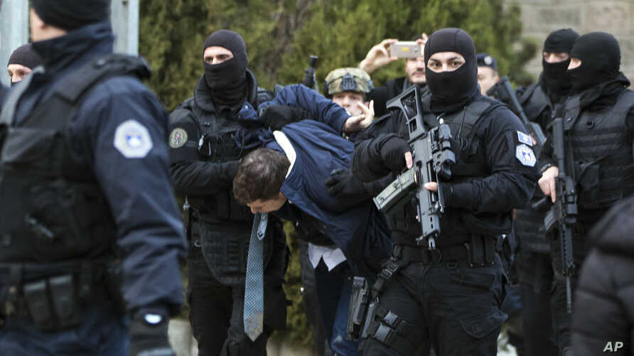 Kosovo police escort Marko Djuric a Serb official to a police station in Kosovo capital Pristina after he was arrested in northern Kosovo town of Mitrovica, Monday, March 26, 2018.