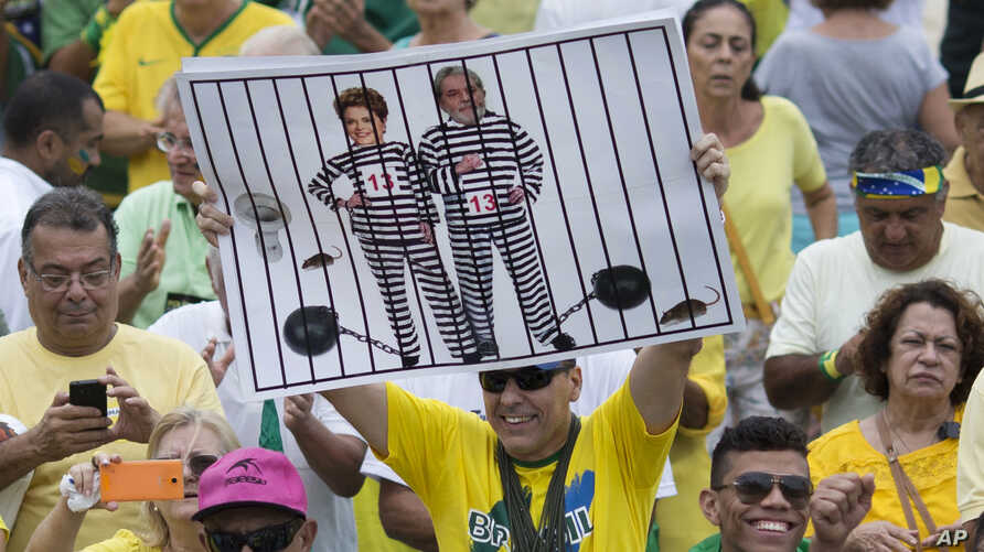 A demonstrator holds a poster with the photo of Brazilian president Dilma Rousseff and former President Luiz Inacio Lula da Silva in prison stripes during a protest on Copacabana beach in Rio de Janeiro, Brazil, March 13, 2016.