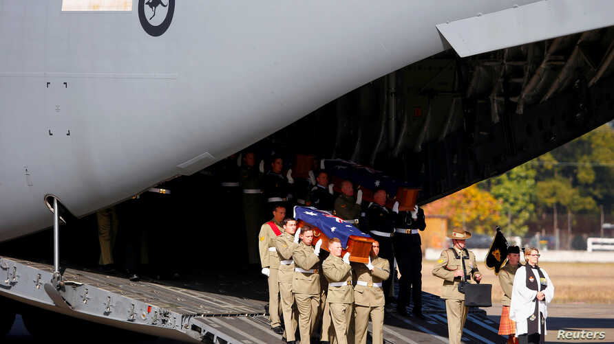 Australian Defence Force personnel carry coffins from a plane that contain the remains of 33 Australian service personnel and dependents, many of whom were casualties of the Vietnam War, during a repatriation ceremony at the Royal Australian Air Forc