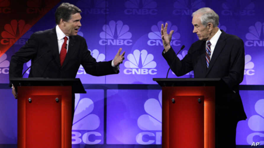 Republican presidential candidates Texas Gov. Rick Perry and Rep. Ron Paul, R-Texas, speak during a Republican Presidential Debate at Oakland University in Auburn Hills, Mich., Nov. 9, 2011.