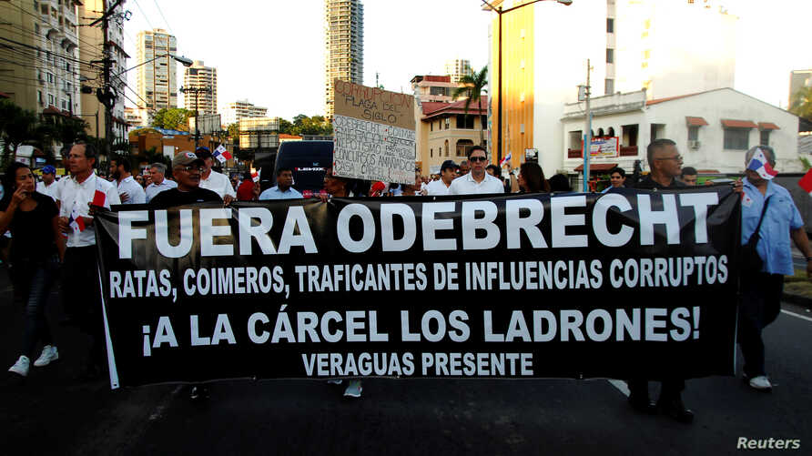 """People take part in a march against the Brazilian construction firm Odebrecht in Panama City, Panama, Jan. 25, 2017. The banner reads """"Get Out Odebrecht, Jail for the thieves."""""""