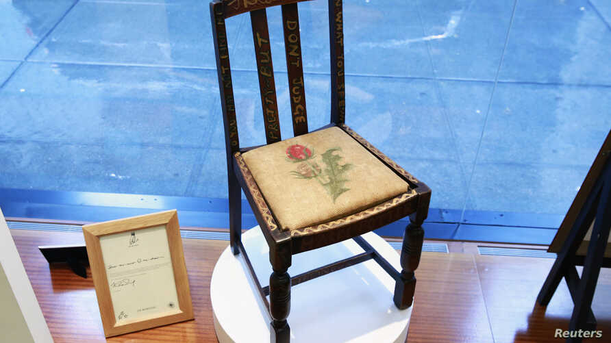 """A chair used by British author J.K. Rowling while writing """"Harry Potter and the Sorcerer's Stone"""" and """"Harry Potter and the Chamber of Secrets"""" is shown in the window of Heritage Auctions in New York, April 4, 2016."""