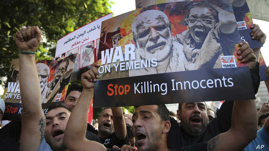Lebanese supporters of the Iranian-backed Hezbollah group, hold placards and shout slogans against Saudi Arabia and the U.S., during a protest to show their solidarity with Yemen's Shiite rebels, known as Houthis, in front the United Nations headquar...