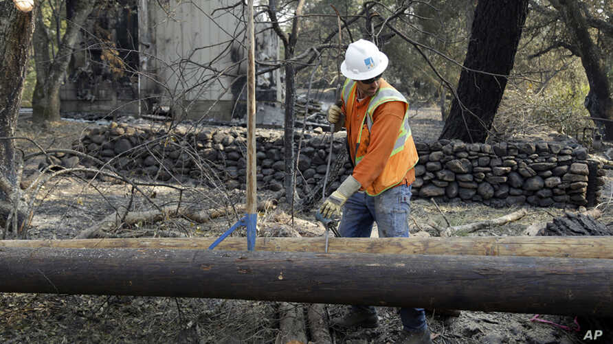 FILE - In this Oct. 18, 2017 file photo, a Pacific Gas & Electric worker replaces power poles destroyed by wildfires in Glen Ellen, Calif. California fire officials say sagging PG&E power lines that made contact ignited a blaze.