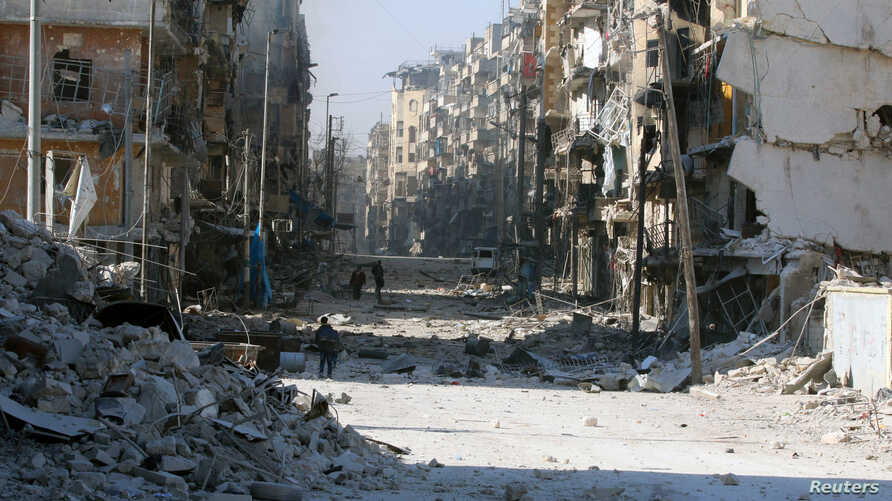 Syrians walk over rubble of damaged buildings, while carrying their belongings, as they flee clashes between government forces and rebels in Tariq al-Bab and al-Sakhour neighborhoods of eastern Aleppo towards other rebel held besieged areas of Aleppo
