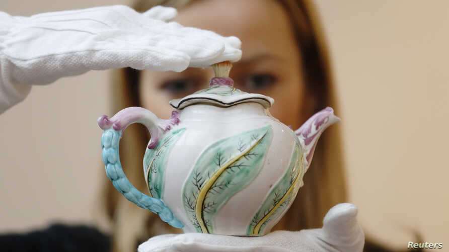 A Sotheby's employee poses with a Chelsea scolopendrium-moulded teapot (dated c.1750), believed to be the only surviving example of this pattern, at Sotheby's auction house in London, May 9, 2014.