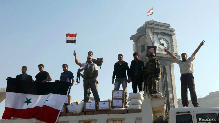 Soldiers loyal to the regime and civilians holding the Syrian national flag stand near boxes containing aid from the Syrian army in Qusair, June 5, 2013.