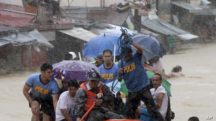 A man dives in the background as rescuers use a rubber dinghy to rescue trapped residents after continues heavy monsoon rains spawned by tropical storm Fung-Wong flooded Marikina city, east of Manila, Philippines, and most parts of  the metropolis, S