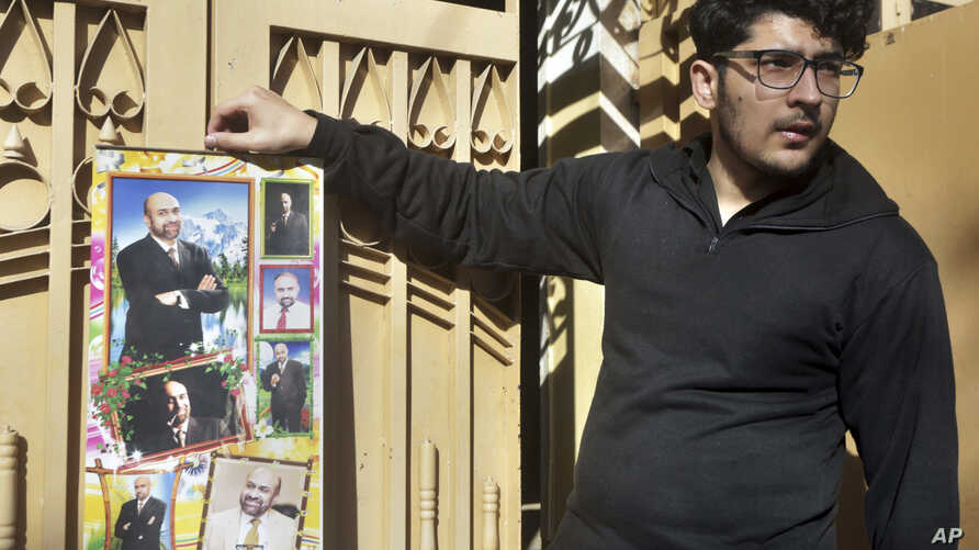 Osama Rizi, son of a journalist Rizwan-ur-Rehman Razi, displays a calendar with the pictures of his father outside his residence in Lahore, Pakistan, Feb. 9, 2019.
