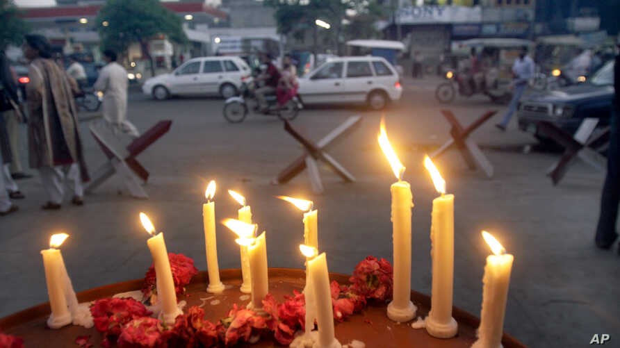 FILE - Lighted candles are seen outside a mosque of the Ahmadi sect, in Lahore, Pakistan, May 30, 2010.