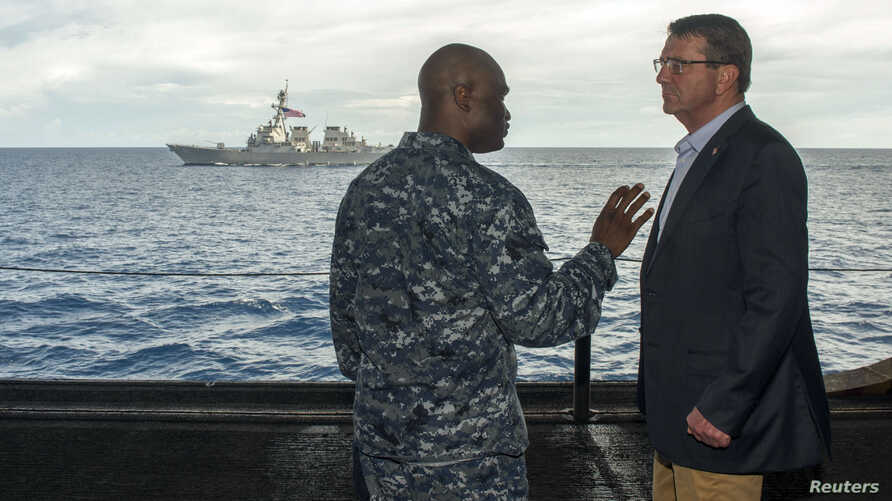 U.S. Secretary of Defense Ash Carter (R) speaks with U.S. Navy Cmdr. Robert C. Francis Jr., as Carter and Malaysian Defense Minister  Hishammuddin Hussein (Not Pictured) visited the USS Theodore Roosevelt aircraft carrier in the South China Sea, in t