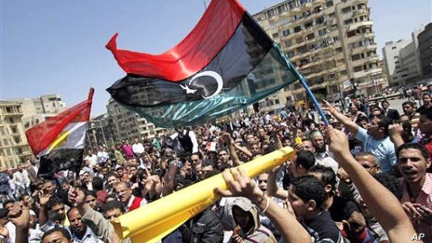 Egyptian protesters wave Libya's old national flag and an Egyptian flag as they demonstrate in the Tahrir square in Cairo, Egypt, April 10, 2011.