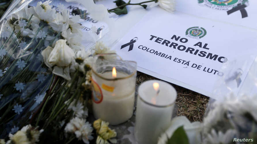 """A sign that reads """"No to terrorism, Colombia is in mourning"""" is seen in front of the scene where a car bomb exploded, in Bogota, Colombia, Jan. 18, 2019."""
