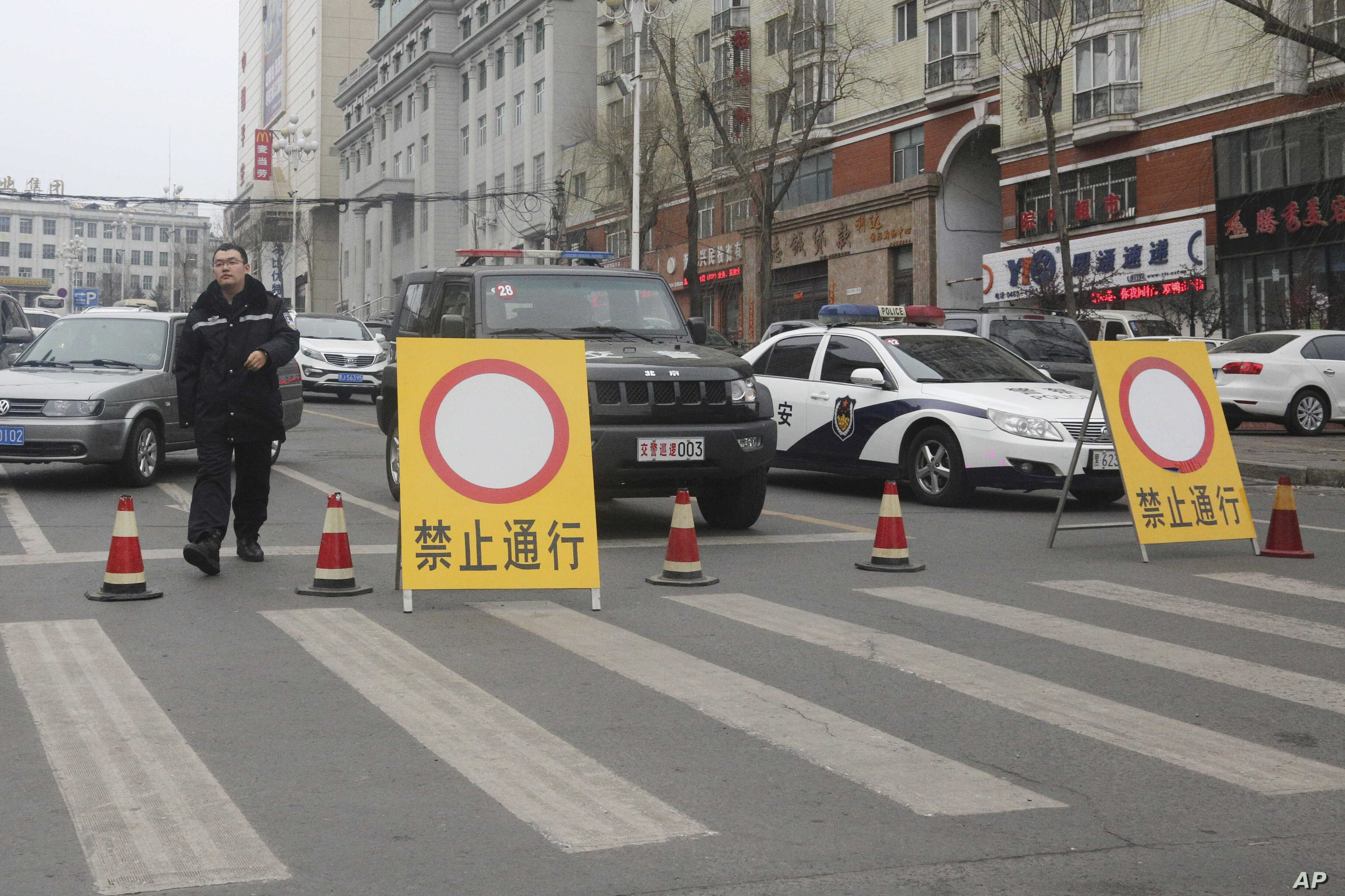 FILE - Police vehicles block a street of the prefectural seat of Shuangyashan after several days of protest by miners over late wages in northeastern China's Heilongjiang province. Frustration among miners over unpaid wages has swelled to the brink o